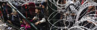 Refugees stand behind a fence at the Hungarian border with Serbia