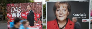 People walk past election campaign posters featuring Germany's Christian Democratic Union (CDU) Angela Merkel (R) and Social Democratic Party (SPD).
