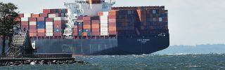 A loaded cargo ship heads out to sea from New York Harbor. Over the past decade, the world's available shipping capacity has grown faster than global trade has.