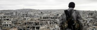 A Kurdish marksman stands on top of a building in the Syrian town of Kobani in January 2015. (BULENT KILIC/AFP/Getty Images)