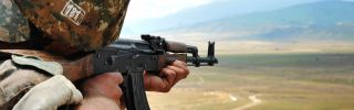 An Armenian soldier of the self-proclaimed republic of Nagorno-Karabakh aims his rifle as he stands in a trench at the frontline on the border with Azerbaijan near the town of Martakert, on July 6, 2012.