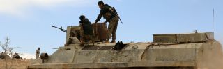 Fighters belonging to the Syrian Democratic Forces sit on an armored personnel carrier in al-Hasaka province on Feb. 19.