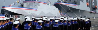 Taiwanese naval personnel walk past a Tuo Chiang-class missile boat in southern Kaohsiung on March 31.