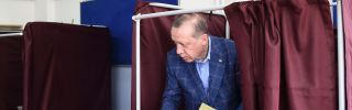 Turkish President Recep Tayyip Erdogan emerges from a voting booth.