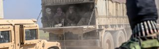 A truck carries men identified as Islamic State fighters on Feb. 20, 2019, near Baghouz, Syria. The fighters surrendered to Kurdish-led Syrian Democratic Forces.