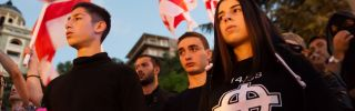 A young Georgian, right, wears a T-shirt with the Stormfront logo and the number 14/88 during a September 2016 rally. The number 14 denotes David Lane's 14-word white supremacist mantra while 88, as the eighth letter of the alphabet, signifies HH, which stands for Heil Hitler.