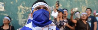In this photograph, demonstrators sing the Nicaraguan national anthem in front of a police station during a protest against President Daniel Ortega's government in Managua on April 25.
