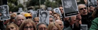 People hold up pictures of victims at a commemoration ceremony 25 years after the terrorist attack on the Jewish community AMIA.