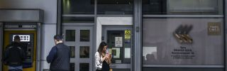 People stand outside a branch of a Piraeus Bank branch in central Athens.