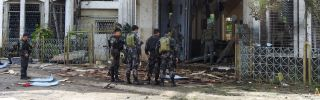 Police officers and soldiers stand outside a Catholic church in Jolo, Philippines, on Jan. 27, 2019, the day after two suicide bombings killed 20 people.