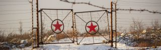 A picture of rusted gates with the star of the former Soviet Union on them.