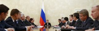 Russian Prime Minister Dmitri Medvedev (C) meets with members of the government's finance and economy ministries in 2014 to discuss policy