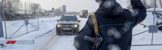 A guard stops a vehicle at Russia's Troyebortnoye border checkpoint on the Russian-Ukrainian border.