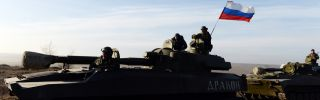 A Russian flag flies near pro-Russia militants sitting atop a 2S1 Gvozdika self-propelled howitzer as a convoy takes a break in the Donetsk region.