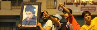 A supporter of Muqtada al-Sadr holds up a picture of the Shiite leader as Iraqis celebrate in Baghdad on May 14, 2018.