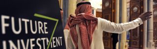 A Saudi man gestures near a sign at the start of the three-day Future Investment Initiative in Riyadh on Oct. 23, 2018.