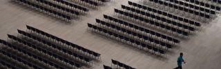 An employee walks between seats ahead of the Siemens company's annual shareholder's meeting.