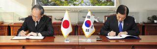South Korean Defence Minister Han Min-Koo and Japanese Ambassador to Seoul Yasumasa Nagamine sign an agreement.