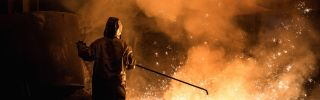 A worker in Germany oversees steel production while wearing protective gear.