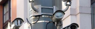 Five surveillance cameras on a lamppost.