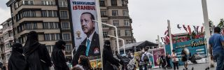"""Pedestrians cross Taksim Square in Istanbul, June 28. The poster behind them shows Turkish President Recep Tayyip Erdogan with a message that read: """"Thank you Istanbul."""""""