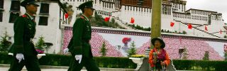 A Tibetan worshiper looks at Chinese police officer patrolling in front of Potala Palace in Lhasa, Tibet.