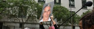 A protest group called Hot Mess holds up signs of Jeffrey Epstein at the federal courthouse in New York City on July 8, 2019.