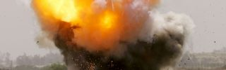 An improvised explosive device explodes next to a road.