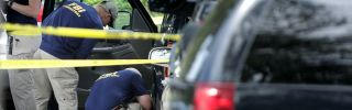 Crime scene experts from the FBI remove evidence from a black SUV on the day after a mass shooting at the Virginia Beach Municipal Center on June 1, 2019.