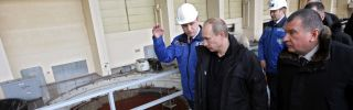 Vladimir Putin walks alongside workers at a hydroelectric plant.