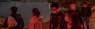 People wear masks against a new coronavirus while walking in Macau on Jan. 28, 2020.