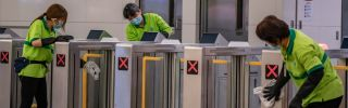 Cleaners wearing protective masks clean the gate in the arrival hall at a Hong Kong rail station on Jan. 29, 2020.