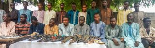 Police officers present suspected ISWAP militants, as well as a cache of weapons, in Maiduguri, northeast Nigeria, on July 18.