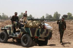 Members of the Kurdish Peshmerga force secure an area west of the northern city of Kirkuk, on June 11.