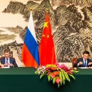Russian Deputy Prime Minister Dmitry Kozak (seated, right) and Chinese Vice Premier Han Zheng (seated, left) sign joint documents following a meeting in Beijing on Sept. 6, 2019. Both officials are seated next to their countries respective national flags.