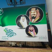 Saudi Crown Prince Mohammed bin Salman (bottom image) and King Salman (left) look out from a billboard promoting Vision 2030 in Jizan, Saudi Arabia, on Dec. 16, 2018.