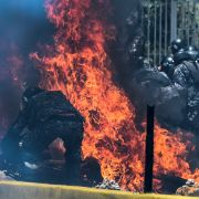 Police officers engulfed in flames from an incendiary device during protests in Caracas on July 30.