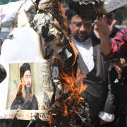 Protesters burn a picture of Islamic State leader Abu Bakr al-Baghdadi on June 9, 2017, in New Delhi.