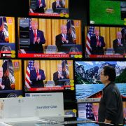 A man at an electronics store in Modiin, Israel, watches U.S. President Donald Trump and Israeli Prime Minister Benjamin Netanyahu unveil the Trump administration's Mideast peace plan during a White House news conference on Jan. 28, 2020.