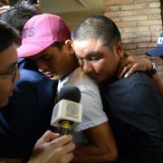 Jaypee Gordiones, Felix Dela Torre and Richard Blaze (left to right), crew members of a fishing vessel that sank after it collided with a Chinese fishing boat off Reed Bank in the South China Sea, are mobbed by journalists following a news conference in Manila on June 28, 2019.