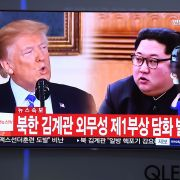 A man walks past a TV showing North Korean leader Kim Jong Un (R) and U.S. President Donald Trump at a railway station in Seoul on May 16.