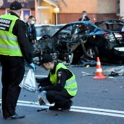 Two Ukrainian police officers investigate a car bombing in Kiev.