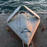 A picture showing U.S. sailors move an X-47B Unmanned Combat Air System (UCAS) demonstrator onto an aircraft elevator aboard the aircraft carrier USS George H.W. Bush.