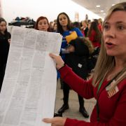 An anti-vaccination parent holds up a prescription document as she waits for a hearing in March 2019 in Washington.