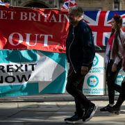 Pedestrians near the British Parliament building pass banners touting Brexit.
