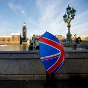 A souvenir stall holder opens a Union Flag umbrella as he arranges his stock opposite the Houses of Parliament on the southern bank of the River Thames in central London.