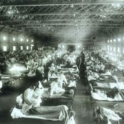An emergency hospital with rows and rows of sick patients in hospital beds at Camp Funston during the 1918 flu pandemic.