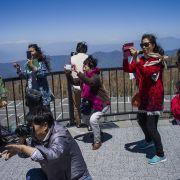 Chinese tourists take photographs at Mount Fuji in Japan.