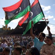In this photograph, Libyans wave their national flag at the port of Benghazi during a ceremony marking its reopening in October 2017.