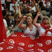 Tunisian women chant slogans and wave their national flag during a demonstration on Aug. 13, 2018, to mark Tunisia's Women's Day and to demand equal inheritance rights for men and women.
